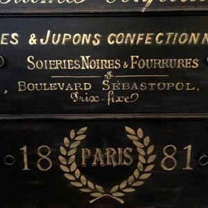 Svart byrå 1800-tal med fransk guldtext och pärllist