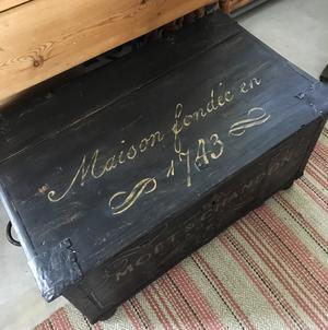 Svart kista soffbord med guldtext