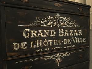 Svart chiffonjé med fransk text Grand Bazar
