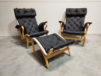 A pair of armchairs, DUX Pernilla 69 with ottoman (Black leather + original upholstery)